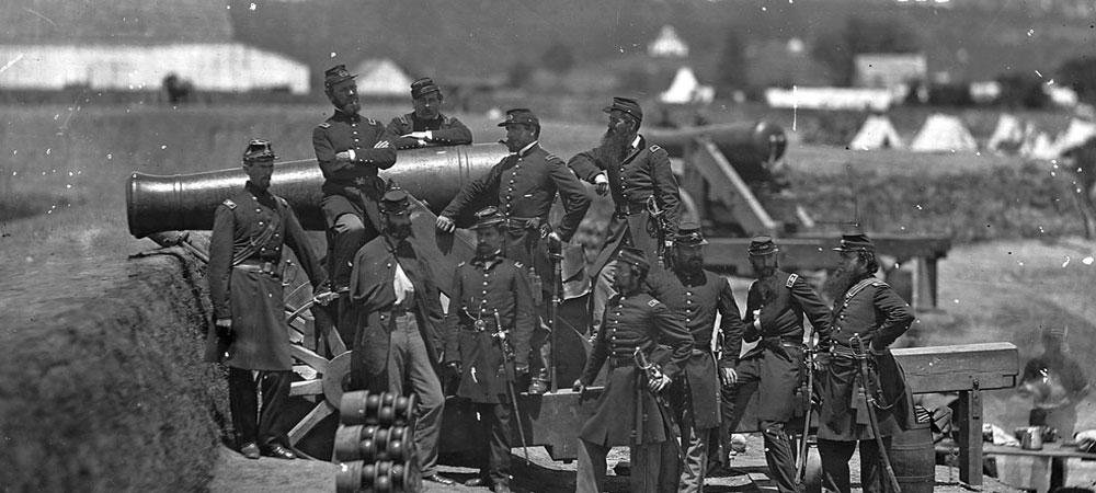 Men posing on artillery piece